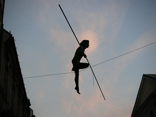 Extreme Leadership: Image is person on high wire w/ balance pole.