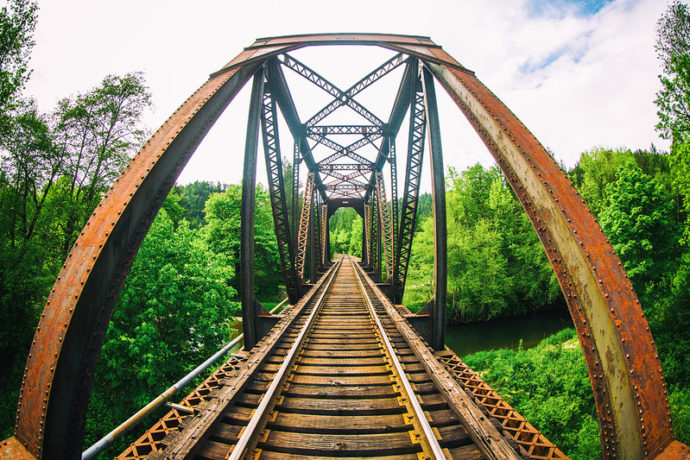 First Career Job: Image is Train Tracks leading through opened sided tressle bridge