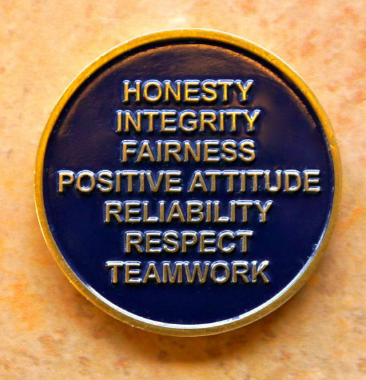 Great employee attitude: Image is a coin saying traits of great attitude.
