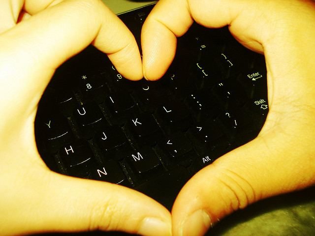 Human Touch: Image is fingers making a heart shape above a keyboard.