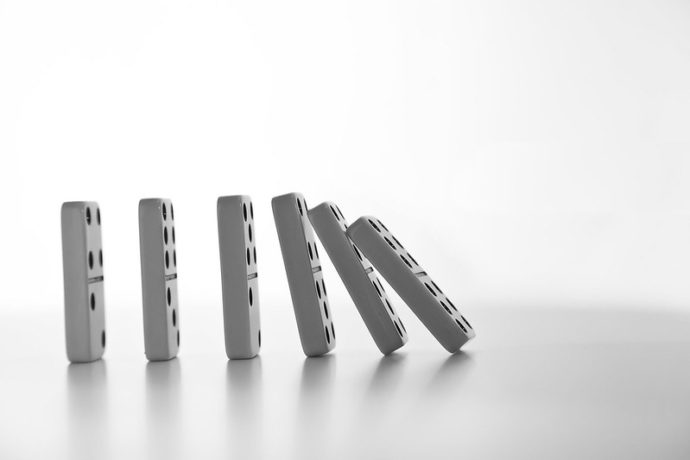 Incompetent Uncaring Leaders: Image is dominoes falling down in a ripple.