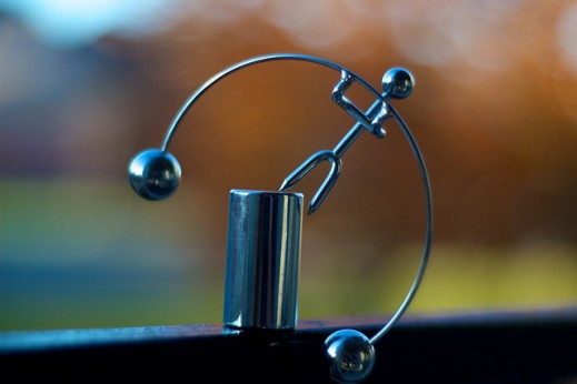 Moderation: Image is a Swinging Desk Toy That Balances in the End