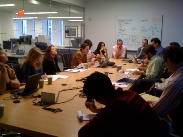 Leadership Reawakening: Image is of business people in meeting w/ flow chart on wall.