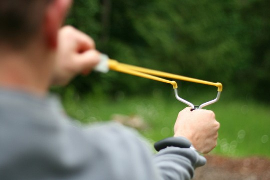Customer Service Recovery, Don't Defend. Image is a sling shot.