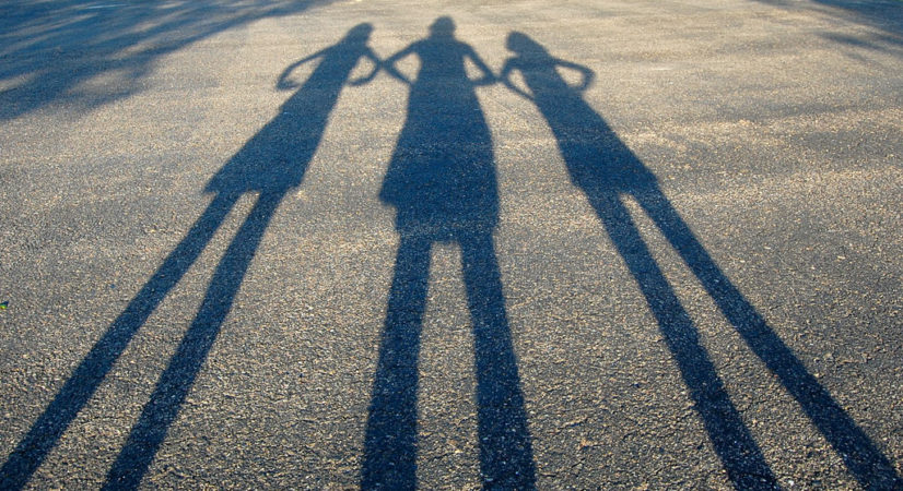 Stop Naysayers: Image is shadow image of three people on a road.