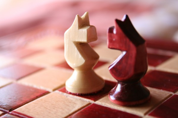 Teamwork Productivity: Image is two chess pieces facing off.