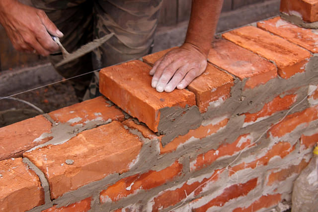 Trivial Leadership Actions: Image is person laying bricks.