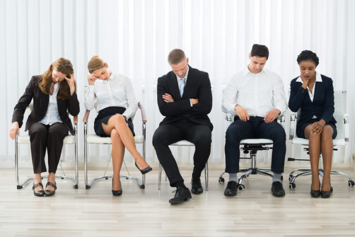 56931342 - businesspeople on a chair sleeping in a waiting room